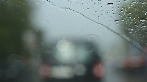Rainy traffic. Looking through windshield at defocused traffic. heavy rain falling and squeaky wipers.