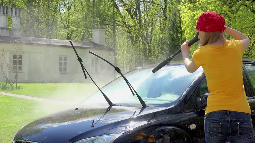 Manual auto wash. attractive woman washing the dirty car with pressured water