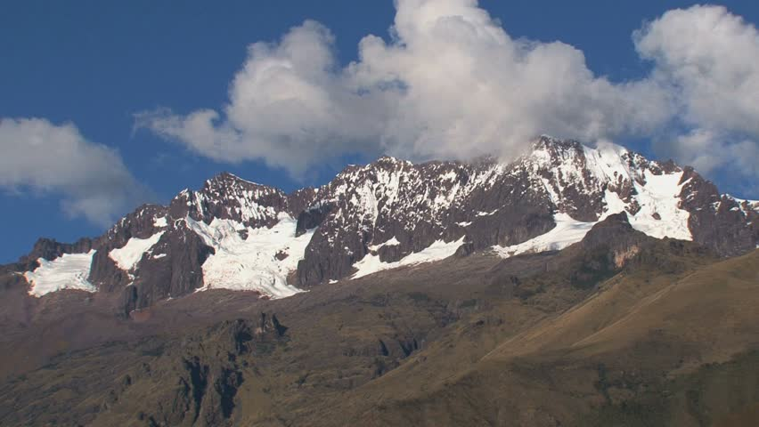 Zoom-out from snow-capped peak to WS of Andean valley