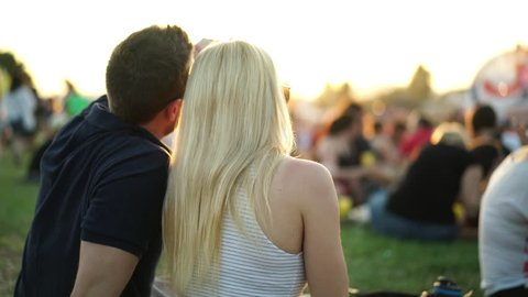 4k footage, couple sitting on festival meadow during summer sunset enjoying open air concert