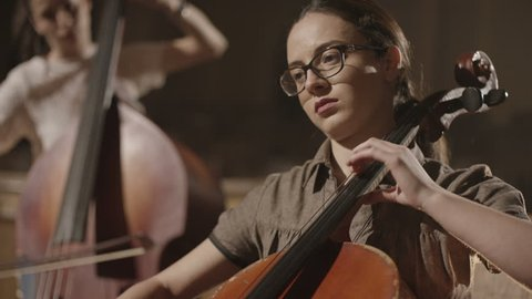 4K Young musician girl playing with cello violoncello in symphonic hall. Shot on RED EPIC Cinema Camera in slow motion.