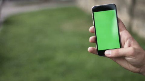 Holding touchscreen device, close-up of female hands using a smart phone   chroma-key, green-screen