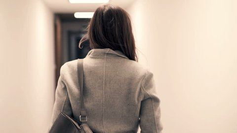 Young woman walking in hall in block of flats