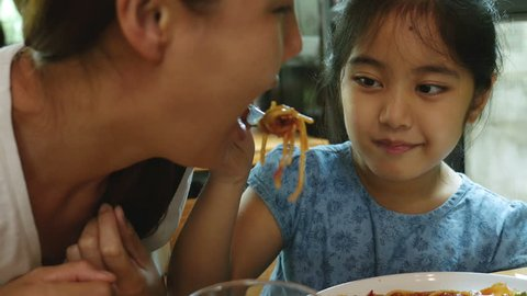 4K : Happy Asian child feeding delicious spaghetti for her mother