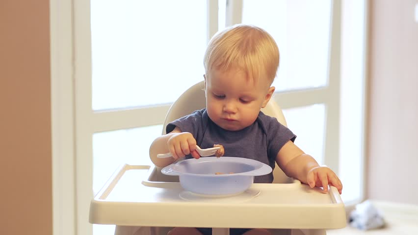 one year old Baby boy with blue eyes is eating with pleasure meatballs with a fork himself from the children's plates. The child learns to eat from a plate independently