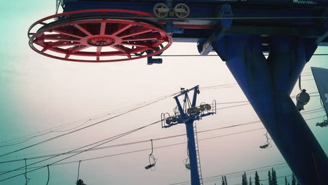 The blue bar of chair lift station on ski resort working and spinning isolate.