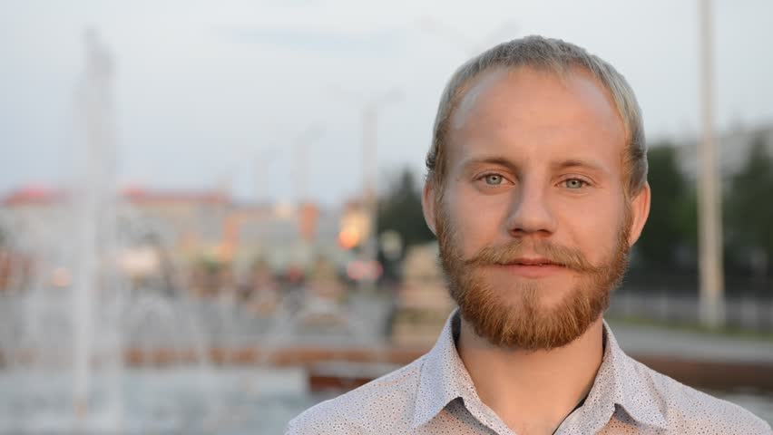 blond man with blue eyes and beard near the fountain looking at the camera #17886397