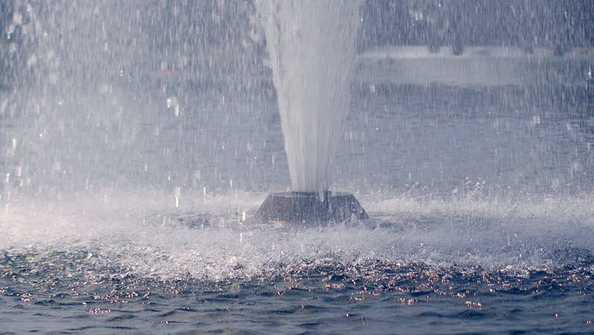 Water drops splashing on water surface in slow motion. Close up of water fountain. Water jet splashing