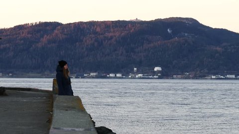 Caucasian woman standin near sea quay and waiting for sunset. Trondheim fjord, Norway.