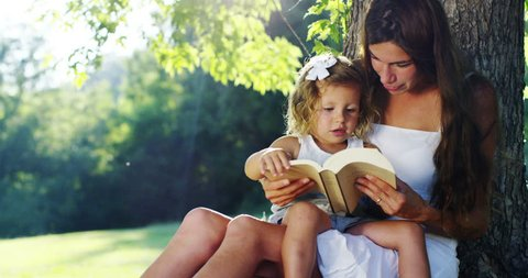 on a sunny day my mother reads to her daughter a book under a tree. relaxing moment between mother and daughter that telling the tale spend time together. concept of mother and daughter