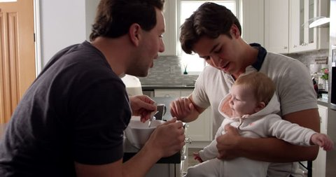 Male couple having breakfast with baby girl in their kitchen, shot on R3D