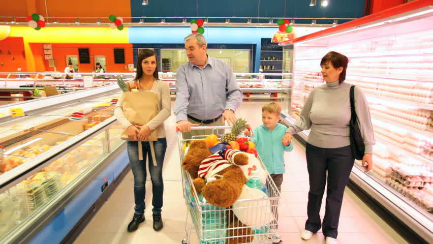 Happy family walking along the shelves in supermarket