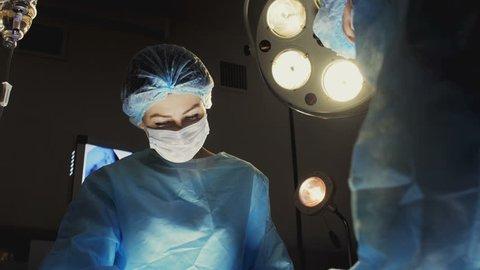 Nurse Assists Surgeon In Operation