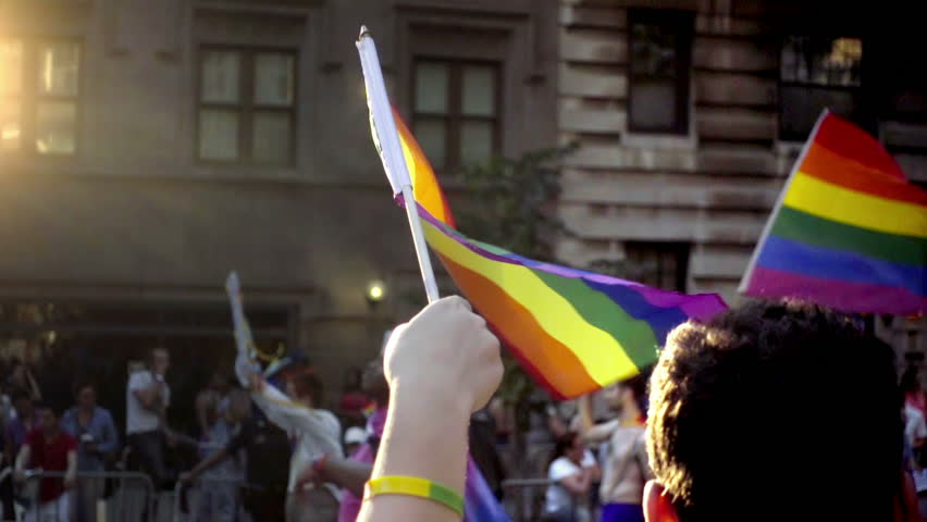 NEW YORK - JUNE 25, 2016: close up on hands waving flags in the annual Gay Pride Parade in NYC. The rainbow colors represent the LGBT.