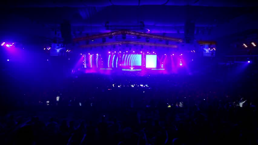 Lot of fans in large stadium at rave party, dj  rises hands on stage, bright light flashes