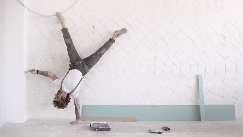 Funny curly man wears pants with suspenders makes sport exercises white painting wall, one hand headstand