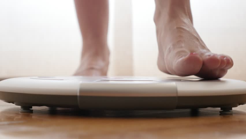 Female measuring weight on health scale close-up 4K 2160p 30fps UltraHD footage - Woman legs approaching to weighing digital instrument 3840X2160 UHD video | Shutterstock HD Video #18032497