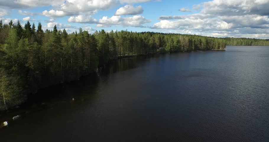 Aerial footage of green forest and blue lake on a sunny cloudy day little bit windy too