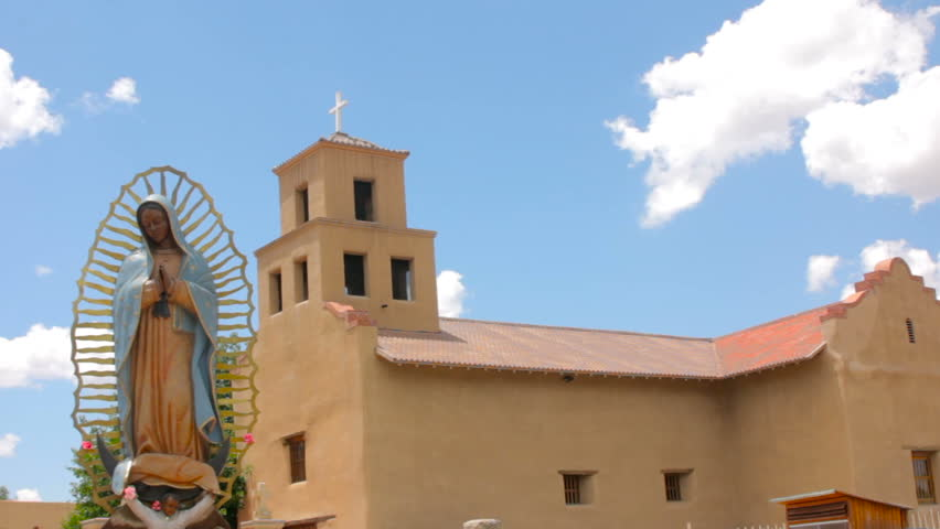 Extreme wide shot of a statue of Our Lady of Guadalupe the Patron Saint of Mexico. The religious icon stands peacefully in front of a historic adobe church in Santa Fe, New Mexico.