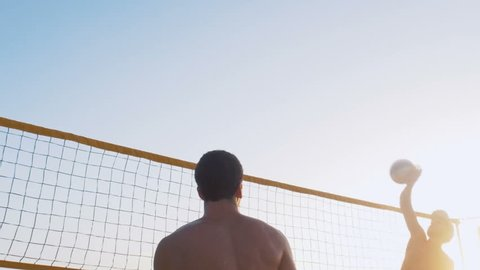 Group of people playing beach volleyball during sunrise or sunset, slow motion