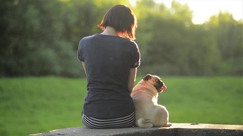 Happy young woman sit back with dog and looking at each other outdoors, girl stroking her mops in a park, warm sunny day