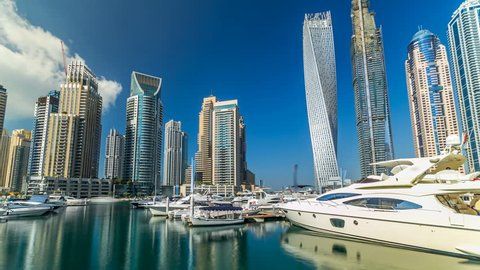 DUBAI - CIRCA JANUARY 2016: Beautiful view from Promenade on Dubai Marina tallest modern Towers and floating yachts and boats timelapse hyperlapse at night, United Arab Emirates. Dubai Marina is a