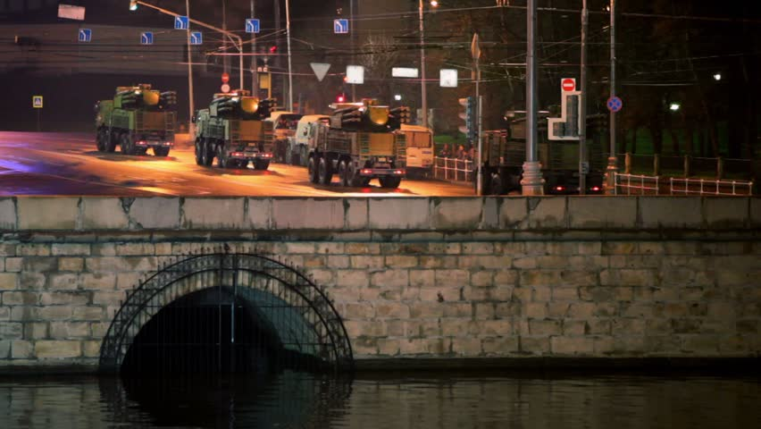 Military motorcade ride by quay at night, many soldiers stands at background