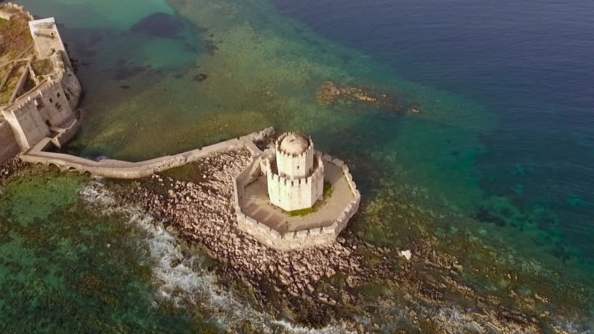 Aerial view from Methoni's Castle in Peloponnese, Greece. The fortress is located by the wonderful sea with rich coloured water. Camera orbits with the old Lighthouse centered.