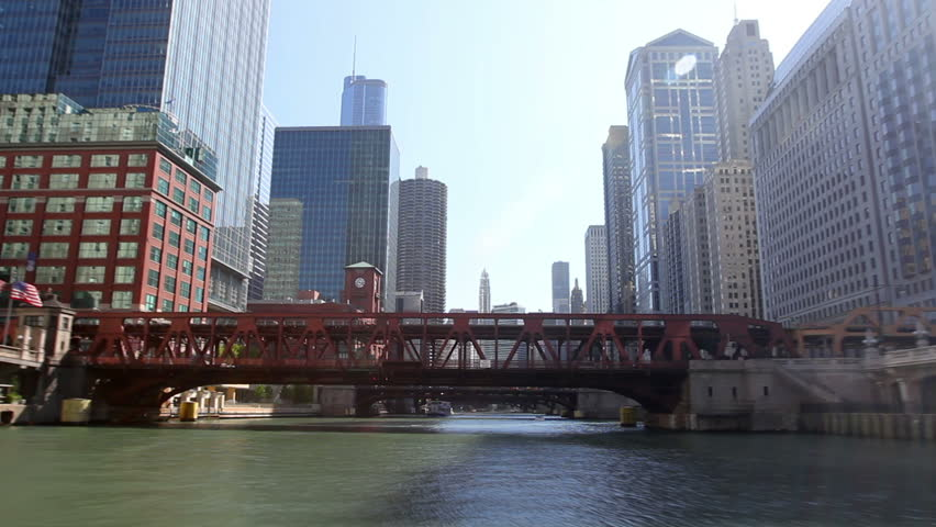 Time lapse shot from a boat as it passes underneath bridges and past the skyscrapers of Chicago on the Chicago River