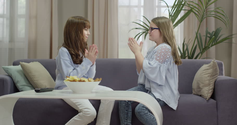 Two Girls Playing Clapping Games On Sofa In Living Room