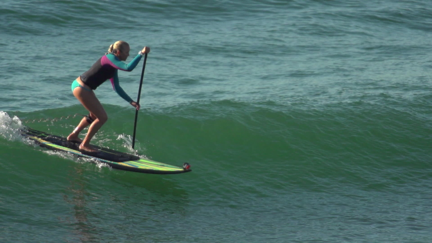 A woman sup stand-up paddleboard surfing at the beach. - Super Slow Motion - Model Released - filmed at 240 fps - Clip is HD 1920 x 1080