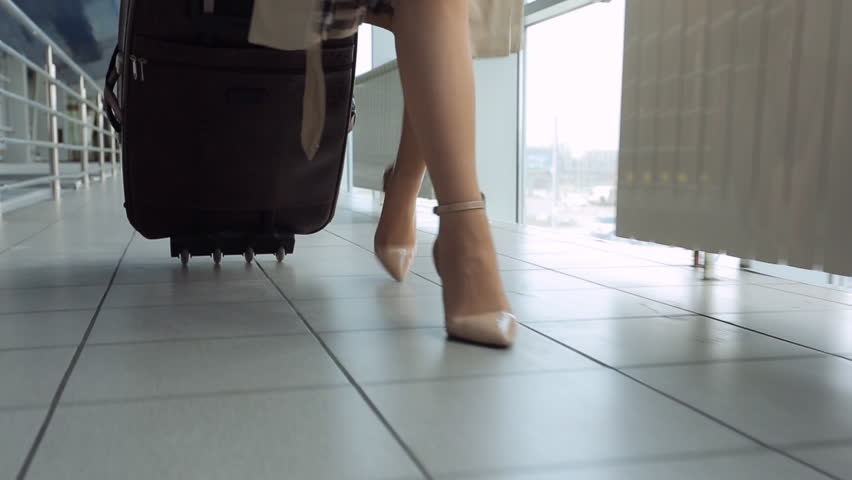 Woman in heels goes at airport and roll suitcase on wheels. | Shutterstock HD Video #18278554