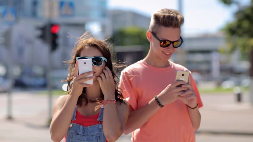 summer vacation, technology, augmented reality and people concept - happy teenage couple with smartphones playing game or shooting video in city