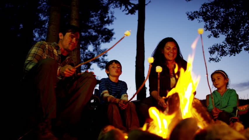 American Caucasian family camping and toasting smores in forest on holiday