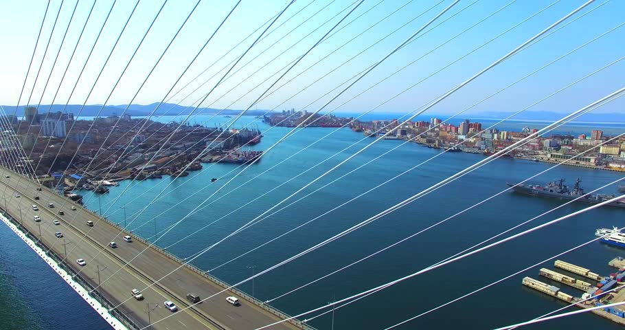 Amazing zooming out aerial view of the Zolotoy Bridge (the Golden Bridge) that is cable-stayed bridge across the Zolotoy Rog built in 2012 in Vladivostok, Russia, and cars driving on it.