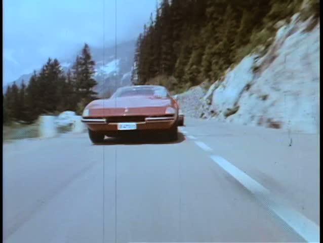 Two cars speeding through mountainside highway