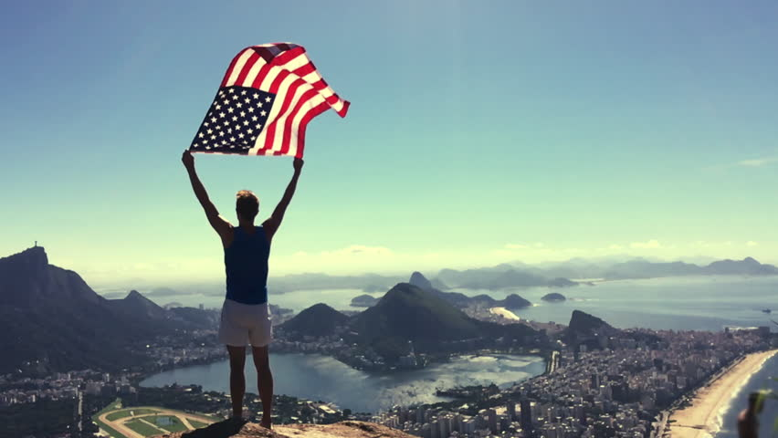 Man stands holding an American flag waving in slow motion at a bright overlook of the city skyline of Rio de Janeiro, Brazil #18402637