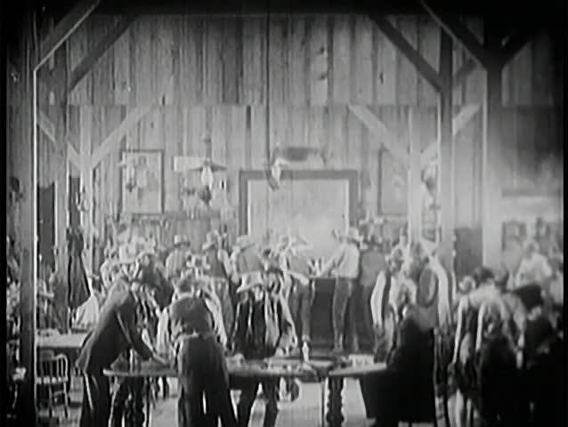 Wide shot of people dancing and gambling in saloon