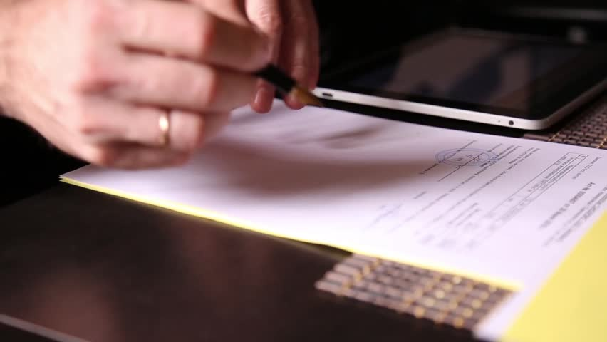 Businessman sitting office desk signs a bill comparing them, with the pc tablet. close-up hands of a man and a fountain pen | Shutterstock HD Video #18421297