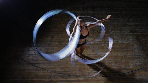 Art gymnastics. Dexterity woman rotate many hula hoop on scene. Top view.