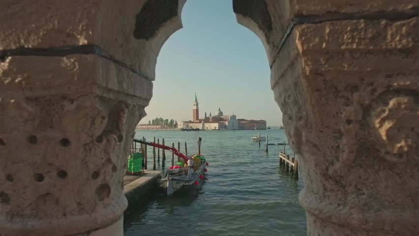 VENICE, ITALY - JUNE 19, 2016: Parking gandolas on the Doge's palace embankment with the bell tower of the Saint Giorgio Maggiore church view, Venice, Italy.