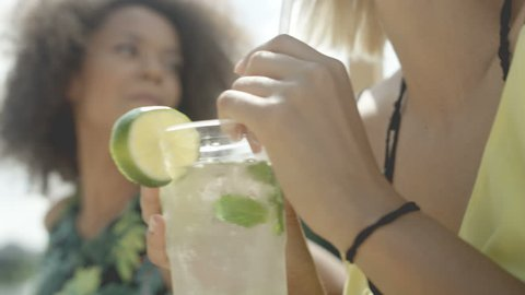 Close up of woman enjoying tropical mojito cocktail decorated with fresh lemon. Two beautiful friends having fun during vacation.