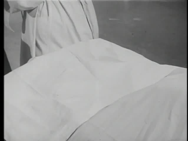 Doctor removing sheet to reveal dead person's hands
