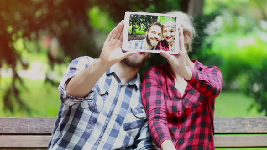 cute modern couple having fun and taking selfies with a tablet in the park, the focus is on the tablet