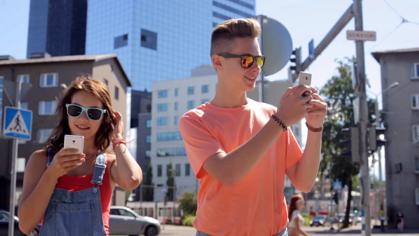 Summer vacation, technology, augmented reality and people concept - happy teenage couple with smartphones playing game or shooting video in city | Shutterstock HD Video #18521537