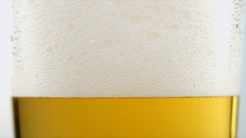 Beer poured into a glass, foam rises and then spills over glass.