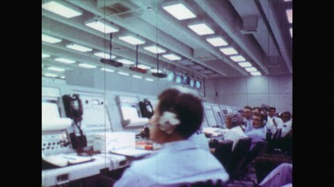 UNITED STATES 1960s:View of People Working at Computer Station in their Headphones. Men Sat Waiting for Space Rocket to Take Off. NASA Mission Control Room