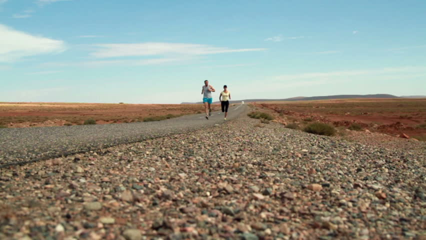 Young couple jogging on the road, slow motion, dolly shot