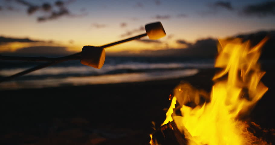Roasting marshmallows over bonfire on the beach at sunset