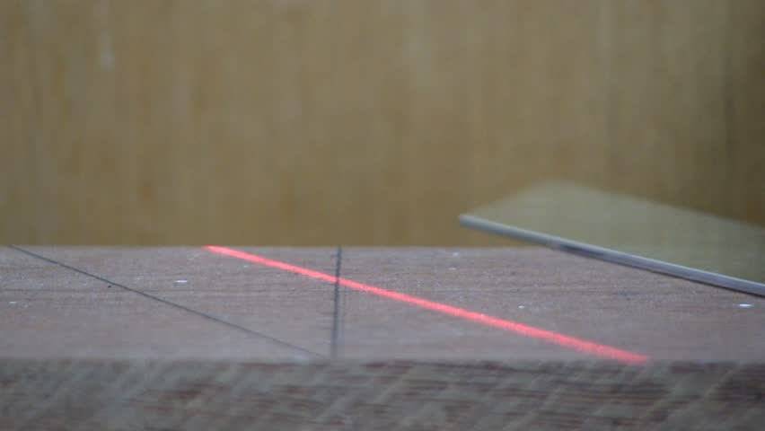 A red laser and adjustable square are used to draw marks in maple board for cutting.  Macro shot from slight high angle looking down with wood background.